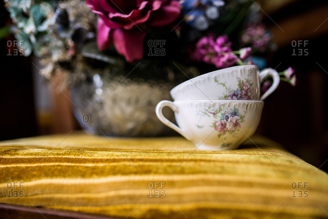 Two vintage teacups stacked on top of one another on table
