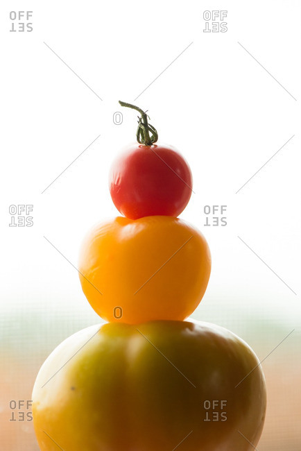 Three colorful tomatoes stacked on top of one another