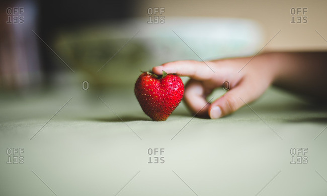 Finger touching a heart-shaped strawberry