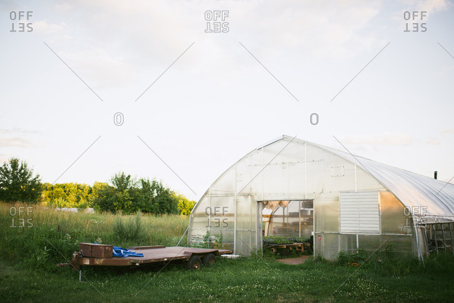 Utility trailer beside a greenhouse