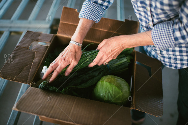 Woman filling a box with vegetables
