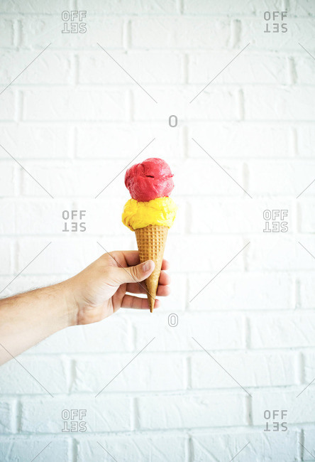 Hand holding a double dip of ice cream