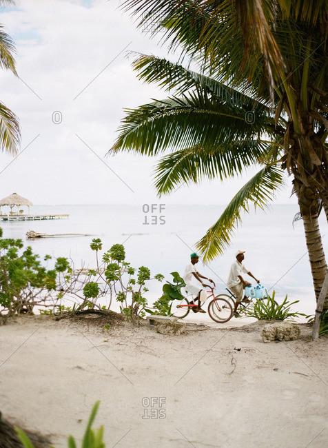 Two men riding bikes riding on a beach