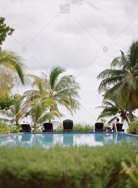 Belize - March 3, 2014: Man relaxing at an oceanside pool