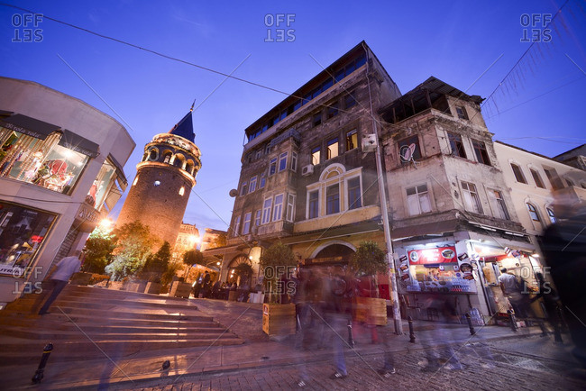 Istanbul, Turkey - October 26, 2012: Pedestrians walking past the Galata Tower at dusk