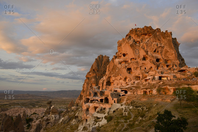 Uchisar Castle carved into a stone mountain at sunset in Cappadocia, Turkey