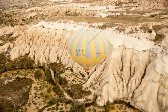 Cappadocia, Turkey - October 26, 2012: Hot air balloon floating over mountain ridges