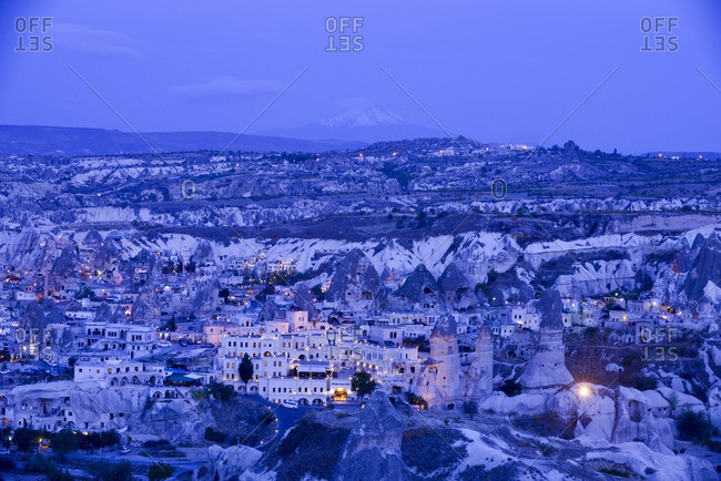 Buildings in Cappadocia, Turkey glowing at twilight with Mount Erciyes in the distance