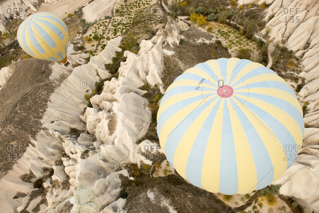 Cappadocia, Turkey - October 26, 2012: Two hot air balloons floating over a mountainous landscape