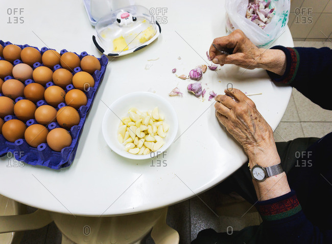 A woman seated at table peeling garlic