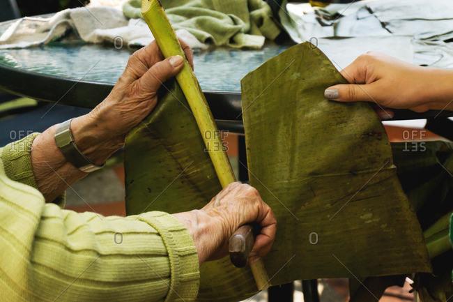 Family members prepare plantain leaves for tamales