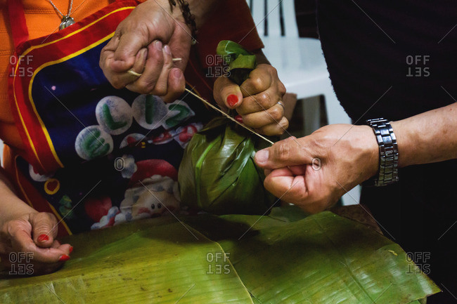 Man ties string around a tamale bundle