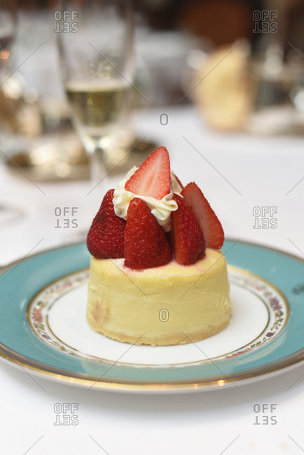 Small white cake with strawberries and whipped cream
