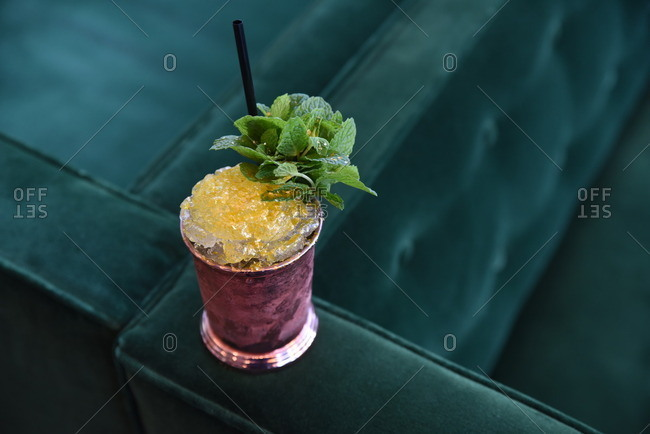 Mixed drink garnished with mint on a blue velvet couch