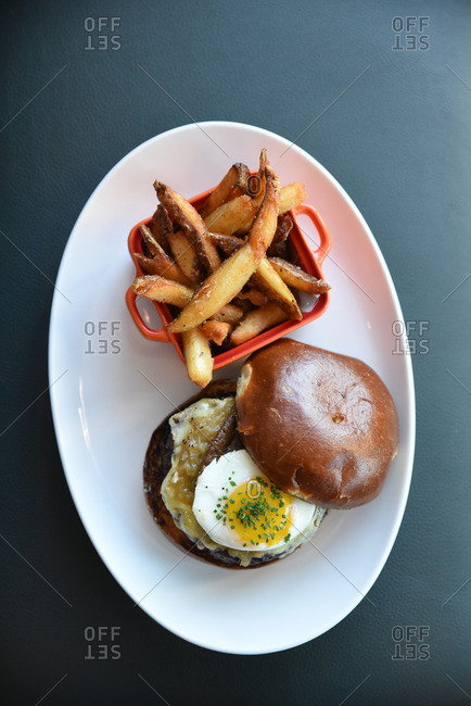 Burger topped with a fried egg and side of fries