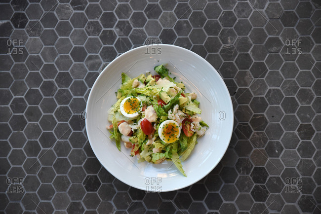 Salad with soft boiled eggs, avocado, tomatoes and chives