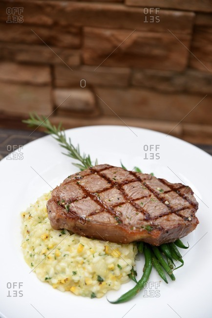 Steak served on top of green beans and corn mash