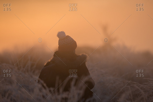 Person walking through frost-covered field at sunrise