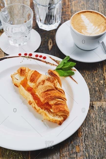 Fresh croissant with cheese and jam served with coffee