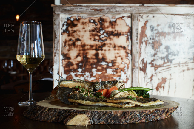 Fish served on wooden board served with wine