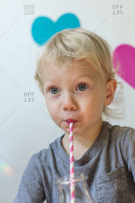 Boy drinking from straw in front of hearts