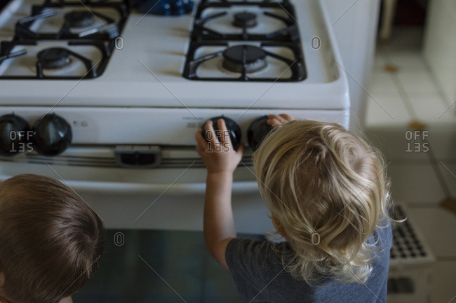 Toddler touching stove knobs