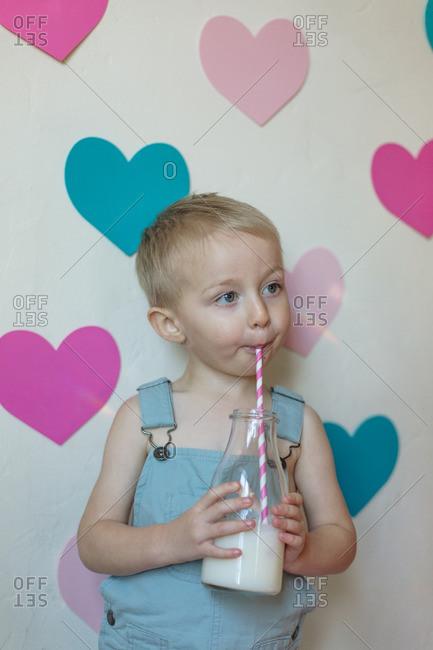 Boy drinking milk by hearts