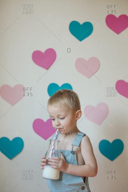 Boy drinking milk by heart cut outs