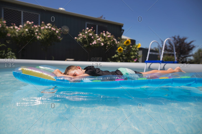 Boy lying on a pool float