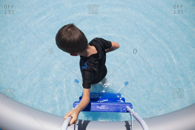 Boy climbing down ladder into pool