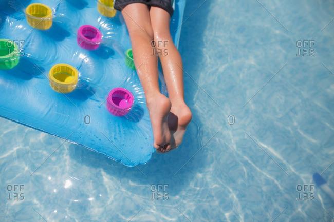 Boy's legs lying on pool float