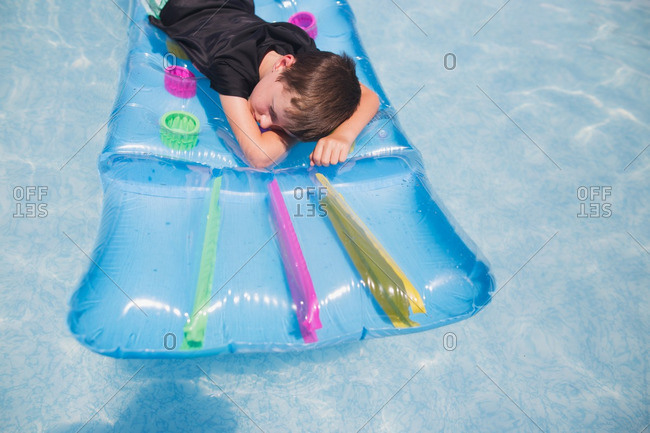 Boy lounging on floating pool raft