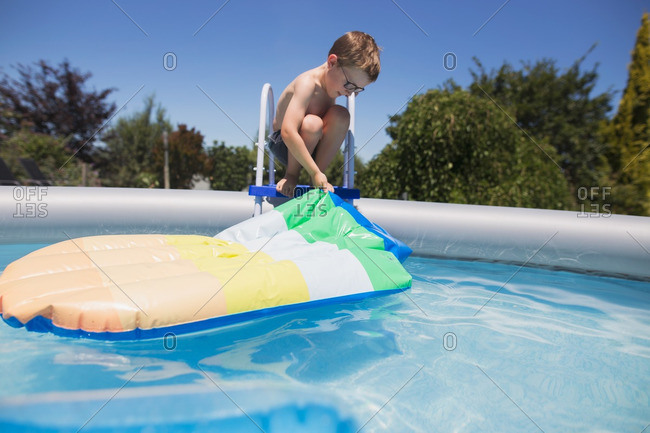 Boy in glasses pulling float out of pool