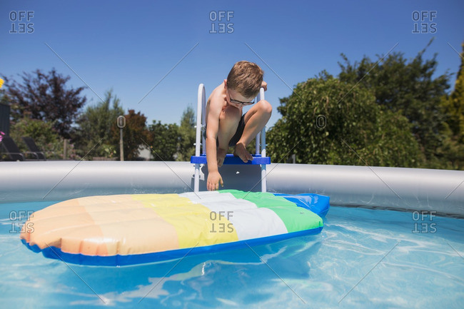 Boy at top of ladder getting pool float