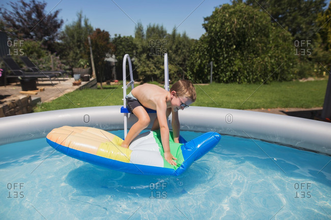 Boy climbing on pool float from ladder