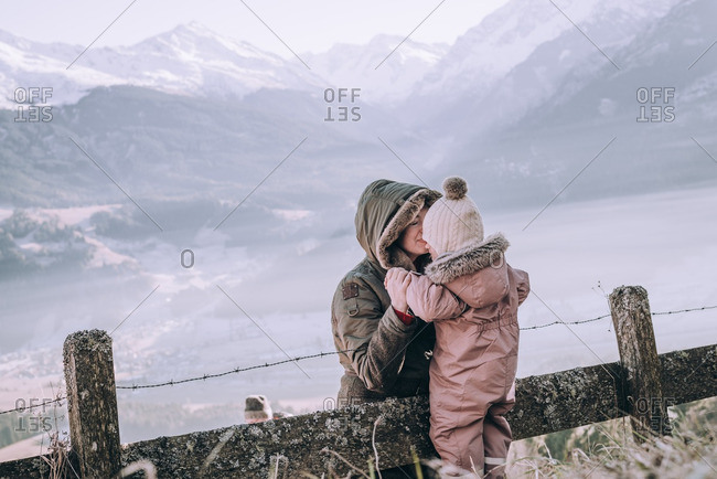 Woman kisses toddler in snowy mountain landscape