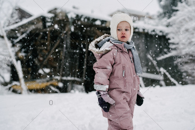 Toddler girl in pink snowsuit watches snow fall