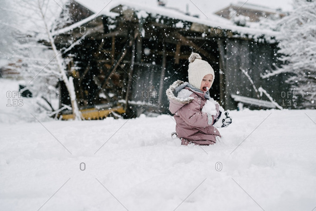 Toddler girl eating snow in backyard