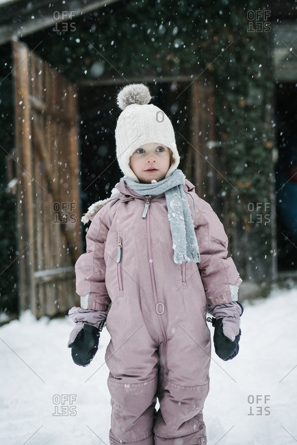 Portrait of toddler girl in a pink snowsuit during a snow storm