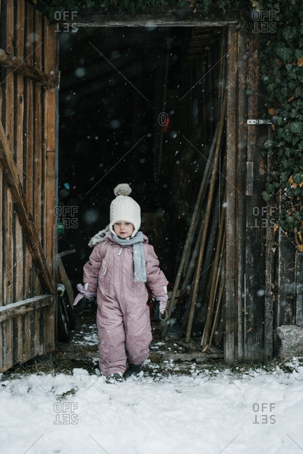 Toddler girl in doorway of barn during snowfall