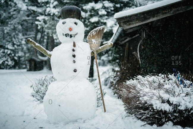 Snowman with broom next to barn in snowstorm