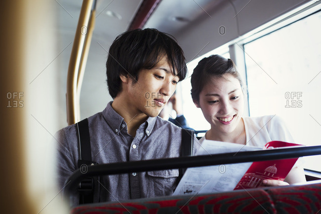 Young Japanese man and woman enjoying a day out in London, riding on a double decker bus.