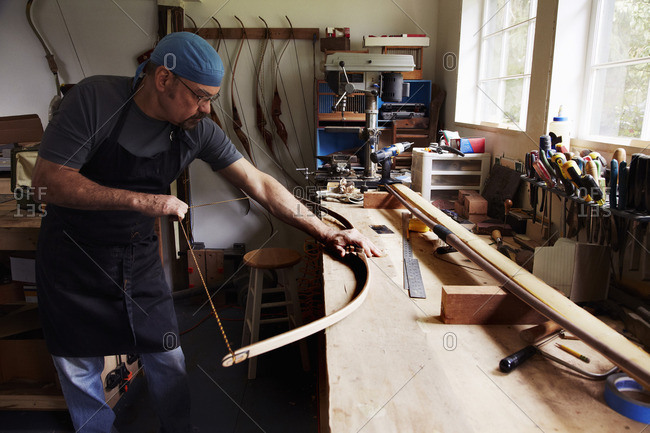 A bowman, a skilled man making a bow, in his workshop.
