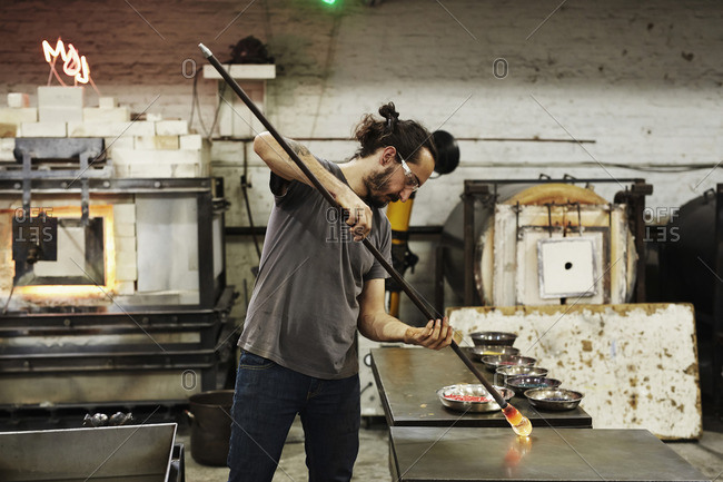 A glassblower holding a piece of molten glass and shaping it on a workbench