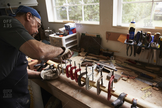 A bow maker working on a wooden bow in his workshop shaping the wood by holding it in clamps.