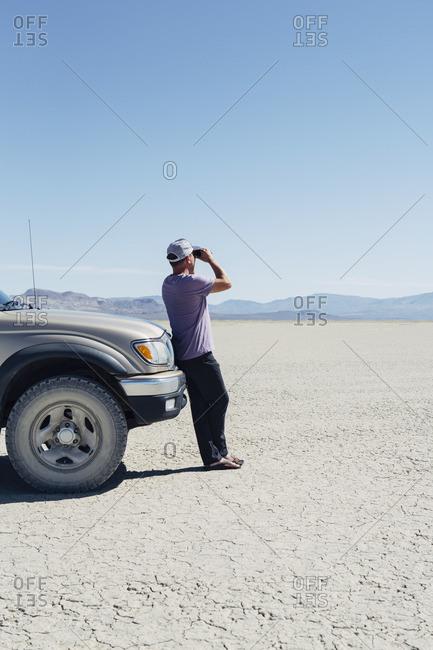 Man standing on vast desert, looking through binoculars and leaning against truck, Black Rock Desert