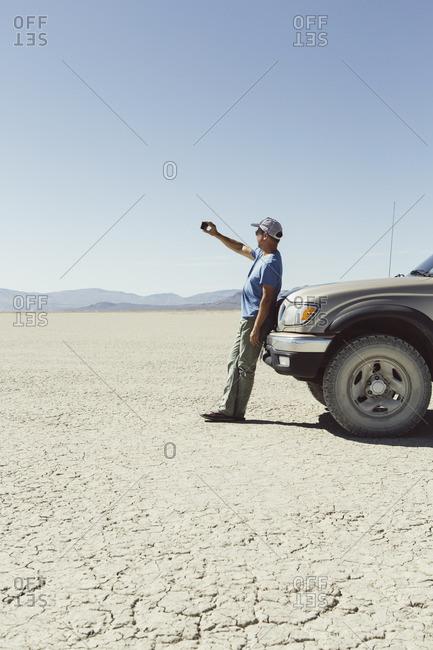 Man leaving against truck in desert, using smart phone, Black Rock Desert, Nevada