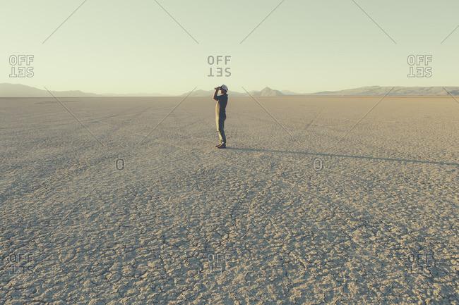 Man standing in remote desert, looking through binoculars, Black Rock Desert, Nevada