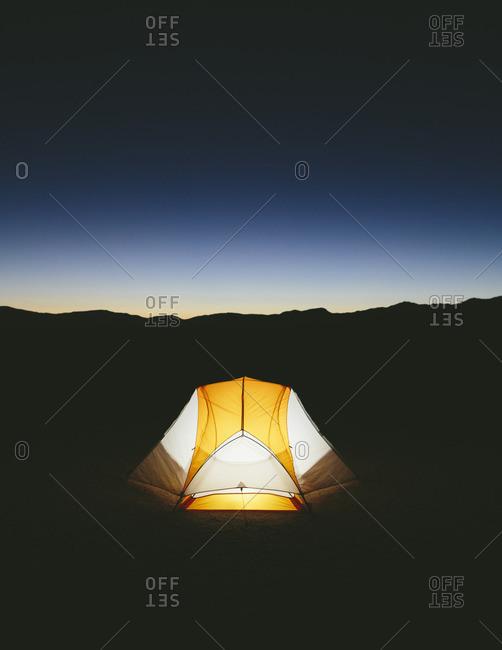 Illuminated camping tent in vast desert at dusk, Black Rock Desert, Nevada