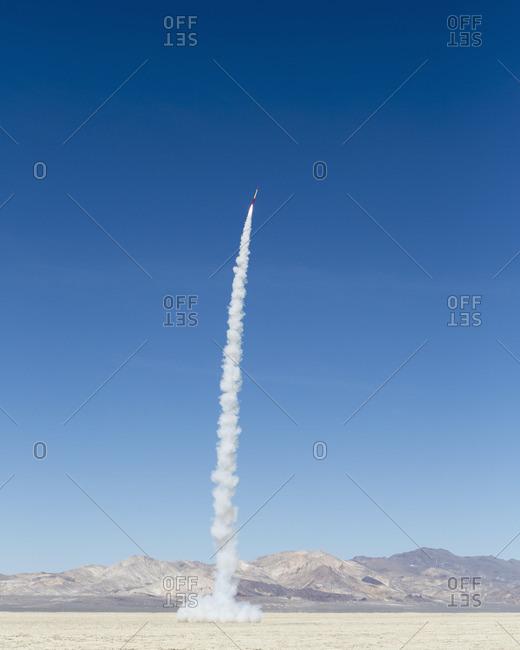 Rocket shooting into vast, desert sky, Black Rock Desert, Nevada